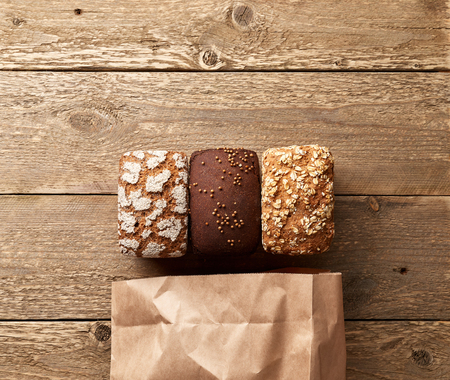 Three loaves of bread on wooden table with paper package. Bakery concept with empty space for design. Gluten-free rye bread with bran and coriander