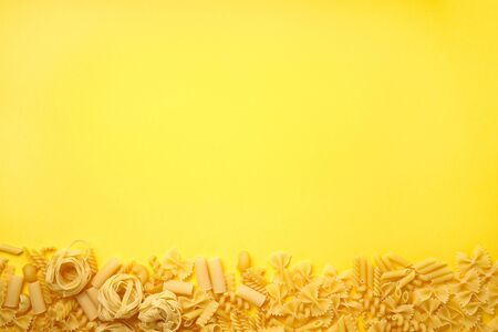 Assorted types of pasta on yellow background. Top view. Various forms of pasta.