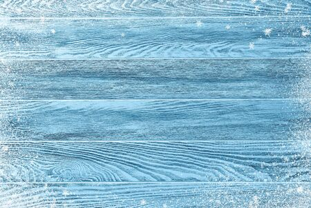 Blue winter wood texture with snow and flakes. Christmas background.