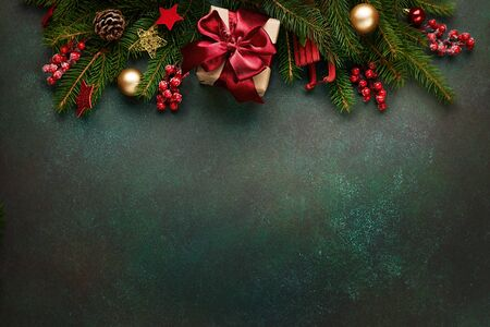 Xmas presents with decoration and fir branches on green background.