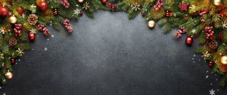 Christmas or New Year banner. Xmas presents with decoration and fir branches on black background.