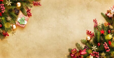 Xmas presents with lights, decoration and fir branches on vintage beige paper. Christmas or new year background for your design.