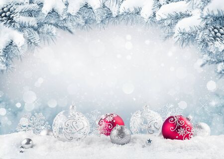 Merry Christmas card. Red christmas balls and baubles on the snow with fir branches.