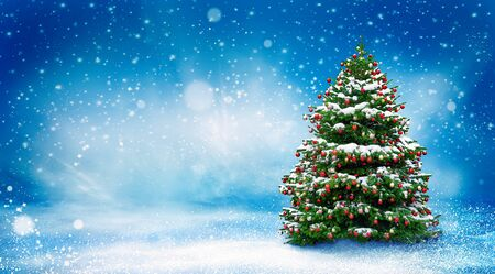Beautiful Christmas snowy background. Christmas tree decorated with red balls in snowfall. Winter landscape.