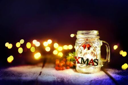 Christmas lights in the glass jar with snow. Winter Christmas bokeh on the holiday card. Reklamní fotografie