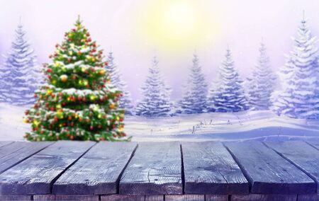Beautiful Festive Christmas snowy background with wooden table. Christmas tree decorated with red balls and in morning forest. Banner format, copy space.
