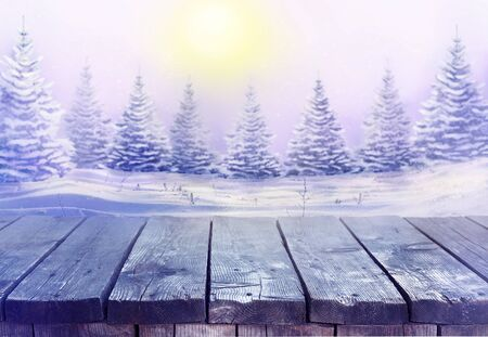 Beautiful festive Christmas snowy background with wooden table. Morning winter landscape with snowy christmas trees. Reklamní fotografie