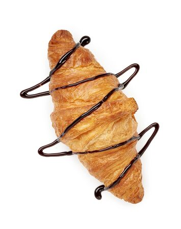 Fresh croissant with chocolate sauce on a white background. Top view.