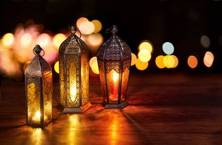 Ramadan lanterns on the table. Dark background with street light and bokehs. Beautiful Greeting Card with copy space for Ramadan and Muslim Holidays. An illuminated Arabic lamp. Mixed media.