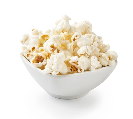 Salted popcorn in white bowl, isolated on white background Imagens