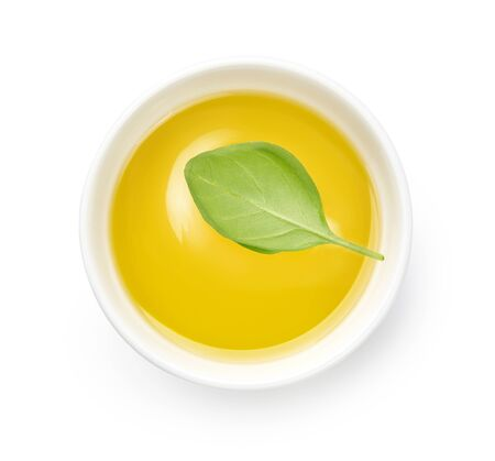 Olive or vegetable oil in white bowl. Top view of oil with basil leaf isolated on white background.