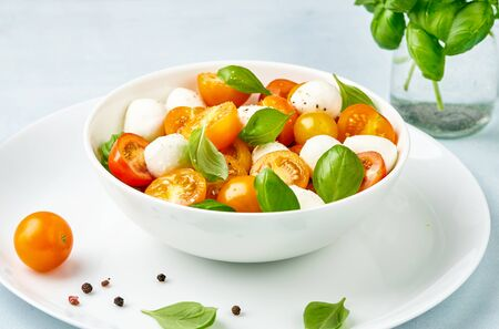 Caprese salad with yellow and red tomato cherry and baby mozzarella cheese in white bowl on white plate. Bocconcini mozzarella cheese with basil leaves.