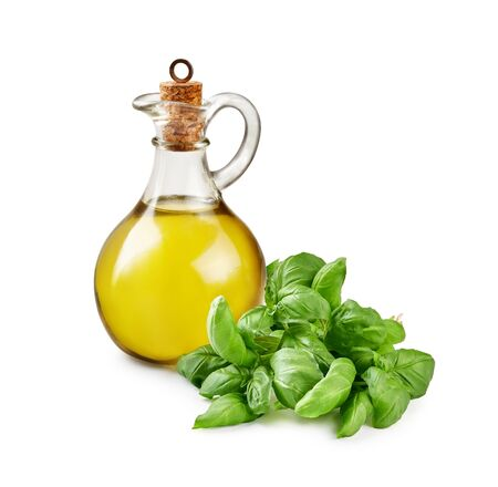 Glass jar of olive oil with basil leaves isolated on white.