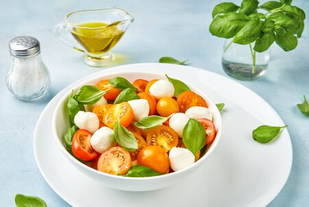 Salad with yellow tomato cherry and mini mozzarella cheese in white bowl on white plate. Bocconcini mozzarella cheese with fresh basil leaves in caprese salad. Imagens