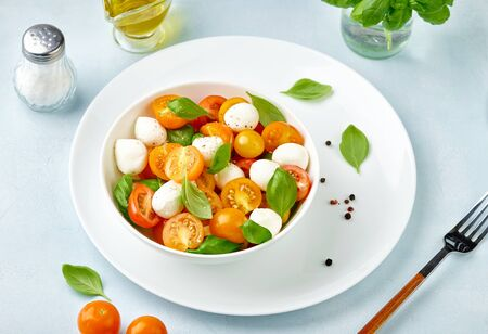 Caprese salad with tomatoes and mini mozzarella cheese in white bowl on white plate. Bocconcini mozzarella cheese with basil leaves.