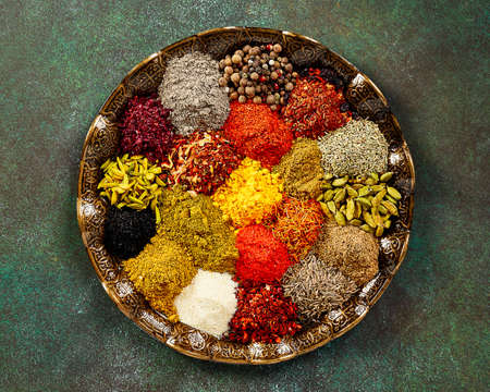 Various spice and dried herbs on oriental plate. Top view of spices