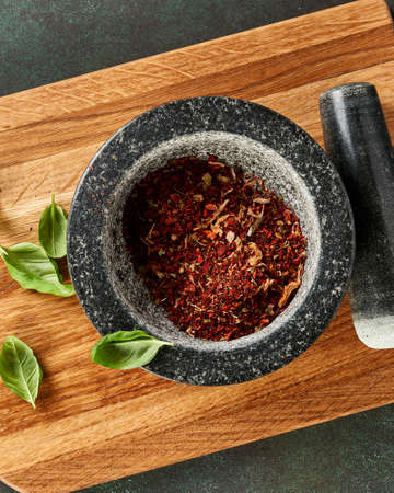 Marble mortar with red pepper, basil leaves and dried tomatoes on wooden board. Top view of spices. Stock fotó