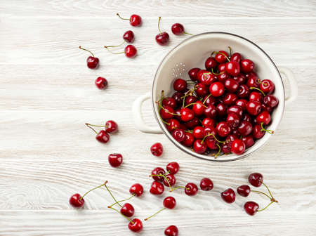 White strainer with fresh cherries on a wooden white background. Top view of colander with cherry berries. Stock fotó
