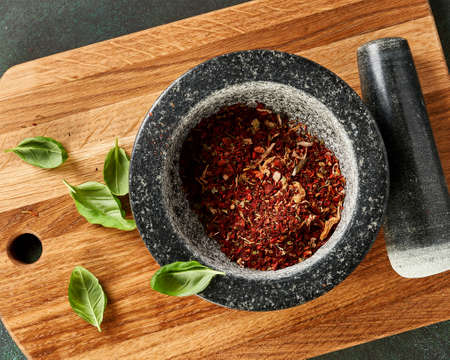 Top view of spices in a marble mortar. Red pepper, spices and basil leaves on wooden board. Stock fotó