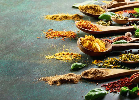 Various spice and dried herbs on dark green background. Stock fotó