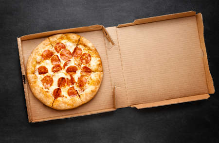 Pizza in a cardboard box on a dark chalkboard. Space for your text. Top view of pizza package. Pizza delivery. Stock fotó