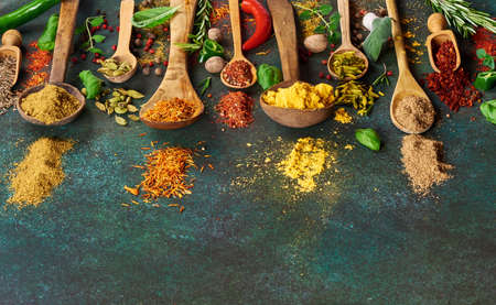 Various spice and dried herbs on dark green background. Top view of spices in wooden spoons