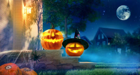 Jack O' Lanterns glowing at moonlight in night. Spooky pumpkin in witch hat. Halloween design with copy space. Halloween pumpkins and decorations outside on porch of house.