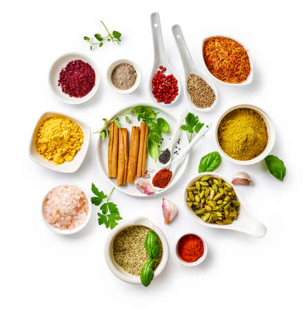 Different indian spices in a bowls and herbs on white background. Top view of indian spices with copy space.