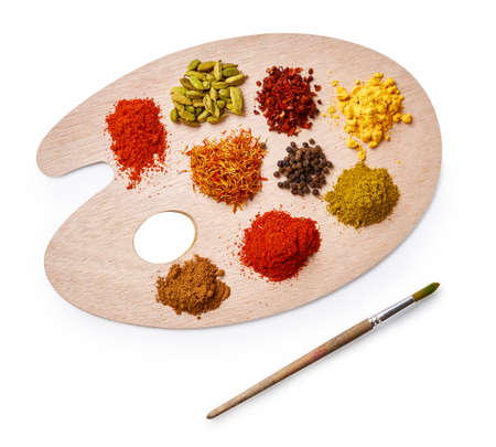 Set of spices on wooden board. Top view of palette with colorful spices isolated on white background.
