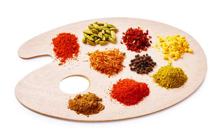 Set of spices on wooden board. Palette with colorful spices isolated on white background.