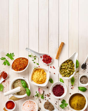 Different indian spices in a bowls and herbs on white wooden background. Top view of indian spices with copy space.