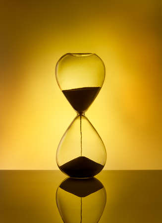 Hourglass as time passing concept for deadline, running out of time. Sandglass on yellow background. Concept of urgency.