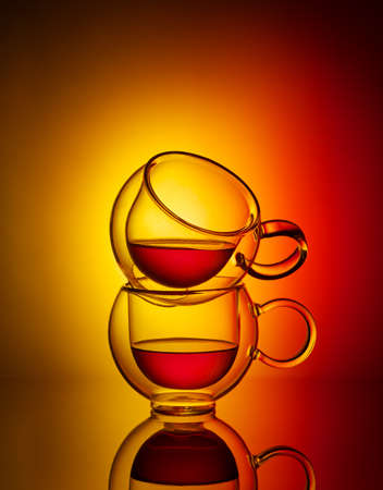 Two glass cup of tea on yellow and red background. Creative concept of tea.