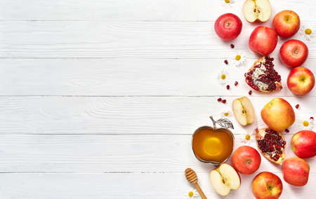 Rosh hashanah (jewish New Year holiday) concept. Traditional symbols. Apples, honey and pomegranates on a white wooden background. Standard-Bild
