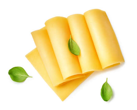 Cheese slices isolated on white background. Top view of cheese with basil leaves.