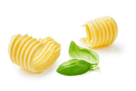 Butter curls or butter rolls with basil leaves isolated on white background