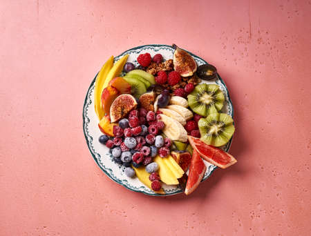 Assorted sliced fruits on vintage plate. Top view of mango, kiwi fruits, figs, grape, bananas, raspberries and blueberries on pink background.