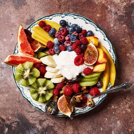 Assorted sliced fruits on vintage plate. Mango, kiwi fruits, figs, grape, bananas, raspberries and blueberries with yoghurt and granola.