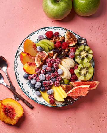 Assorted sliced fruits on vintage plate. Top view of mango, kiwi fruits, figs, grape, bananas, green apples, peach fruit, raspberries and blueberries on pink background.