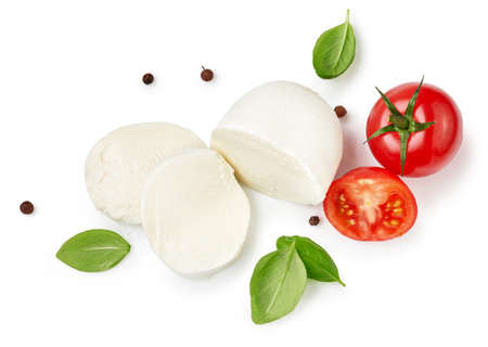 Pieces of mozzarella Buffalo cheese with basil leaves. Top view of sliced cheese with tomatoes isolated on white background. Zdjęcie Seryjne
