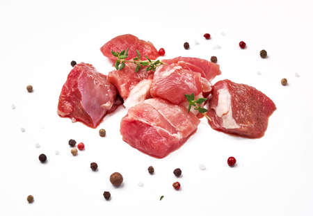 Sliced mutton meat with thyme herb and mix peppers isolated on white. Pieces of raw mutton meat.