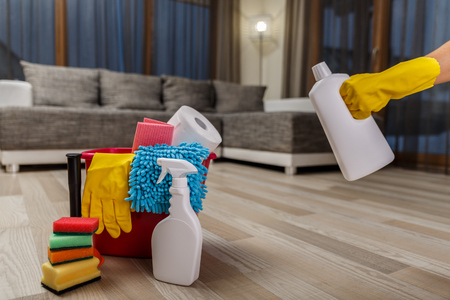 office cleanup: Cleaning service. Bucket with sponges, chemicals bottles and plunger. Hand in rubber glove holding a bottle. Paper towel. Household equipment.