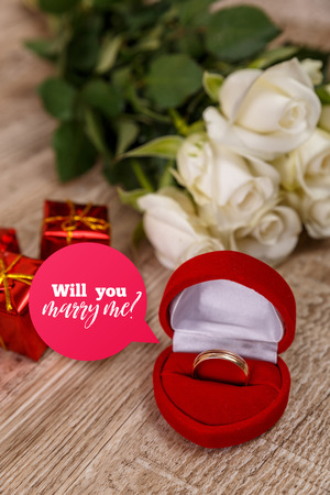 White roses with engagement ring. Will you marry me design. Valentines day concept. Fresh natural flowers with gift boxes. Wooden rustic board.