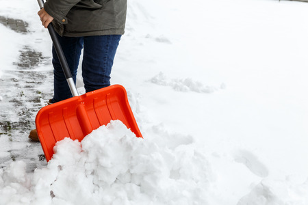 shoveling: Woman with shovel cleaning snow. Winter shoveling. Removing snow after blizzard. Stock Photo