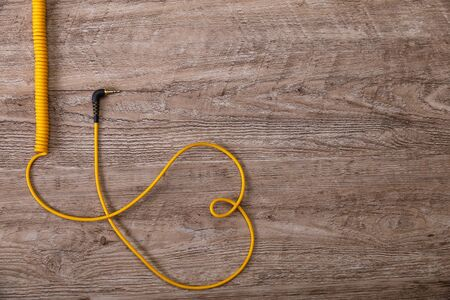 Heart of yellow headphones cable. Love listening music. Socket jack lying on wooden rustic background.