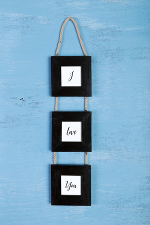 scraped: Blank photo frames on blue wood background. I love you concept. Painted scraped wooden board. Grunge plywood texture or pattern. Stock Photo