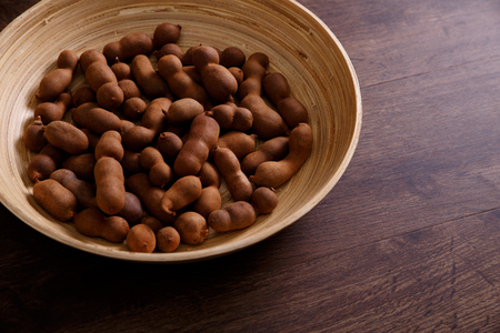 riboflavin: Sweet tamarind on grunge rustic wood background. Natural organic diet food with a lot of vitamins. Plate dish or bowl on wooden board.
