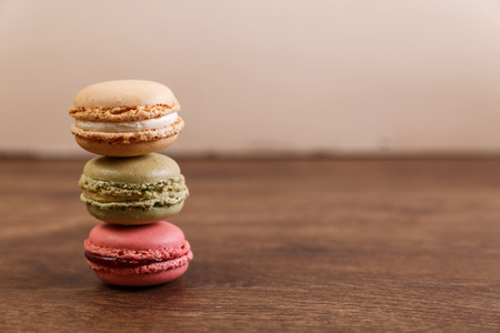 Macaroon cakes. Different types of macaron. Colorful almond cookies. French sweet dessert. Wooden rustic board. Stock Photo