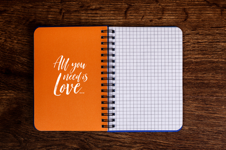 stationery needs: Notepad with All you need is love text. Mockup design concept with empty notebook page. Mock-up of blank diary. Wooden rustic desk. Stock Photo