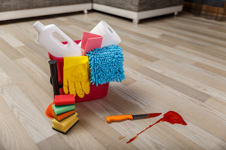 Crime cleaner concept. Bucket with sponges, chemicals bottles and plunger. Paper towel. Knife and splash of blood. Stock Photo